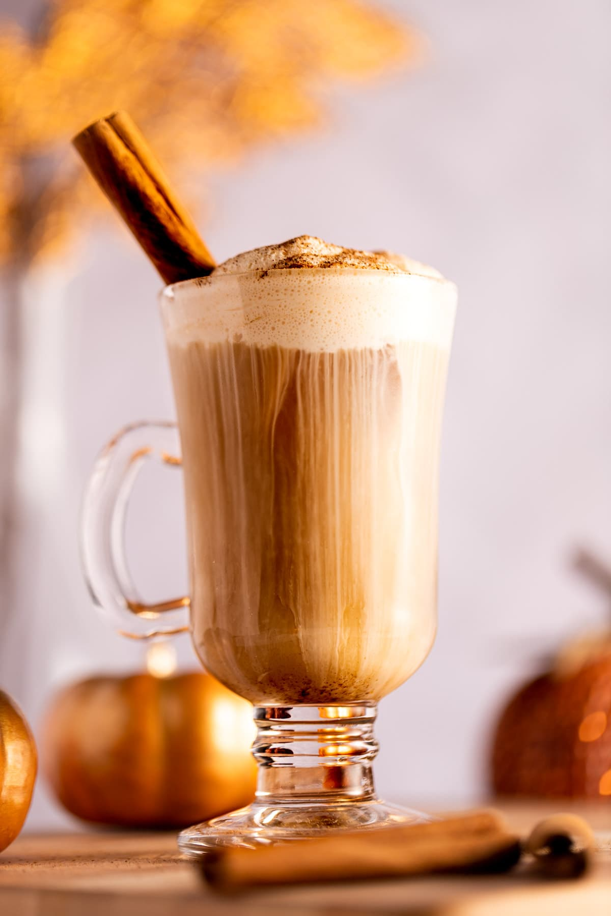 Up close view of an iced chai tea latte topped with pumpkin cold foam, a cinnamon stick sticking out of the glass and cold foam cream dripping down into the latte, decorative pumpkins in the background.