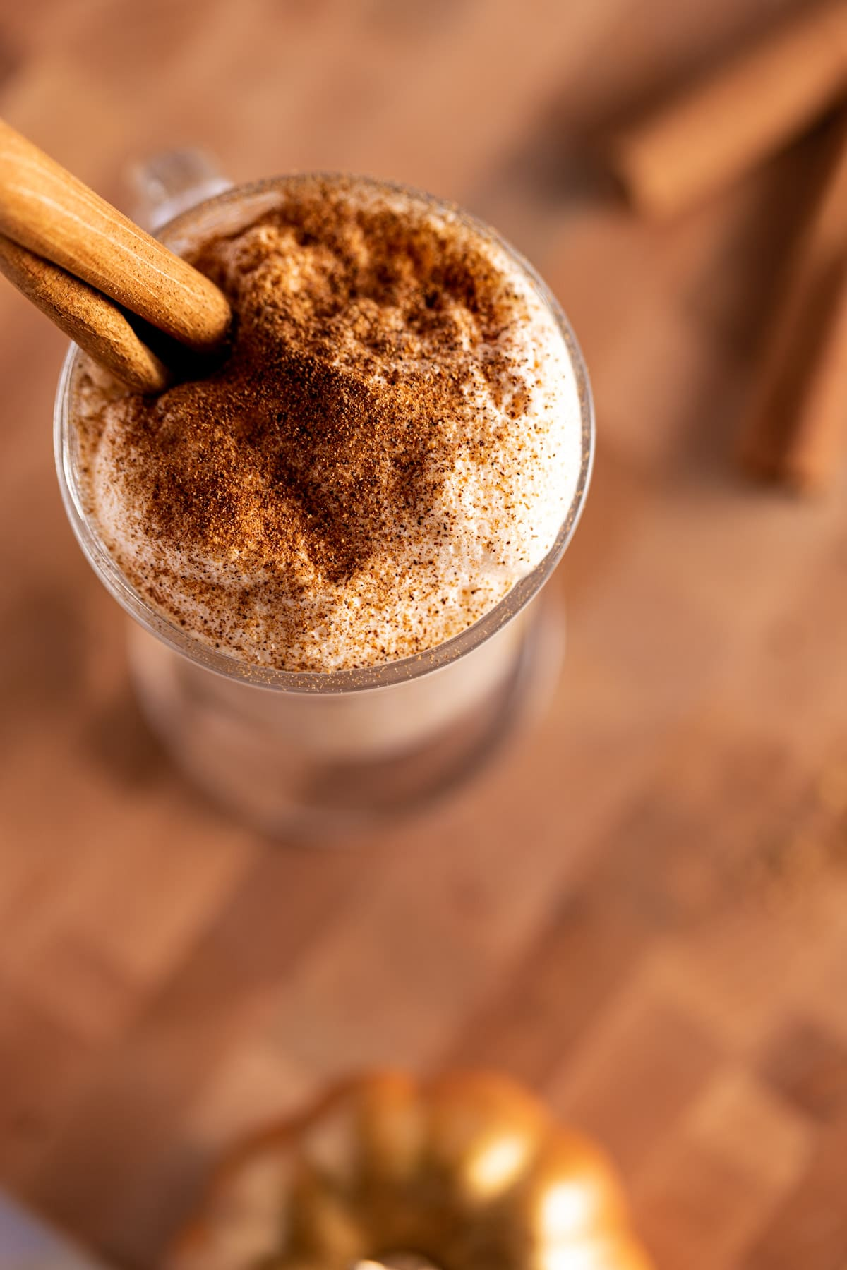 Overhead photo of an iced latte with pumpkin foam on top, on a wooden board, with golden decorative pumpkins around the glass.