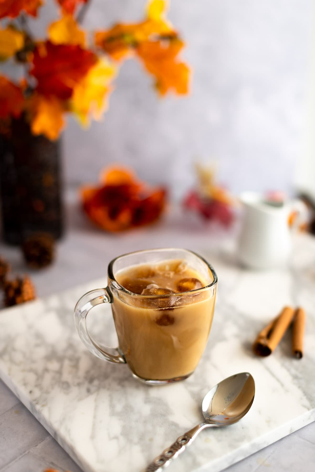 Iced chai latte on a white marble board, next to a metal spoon, cinnamon sticks, with leaves and pinecones in the background.
