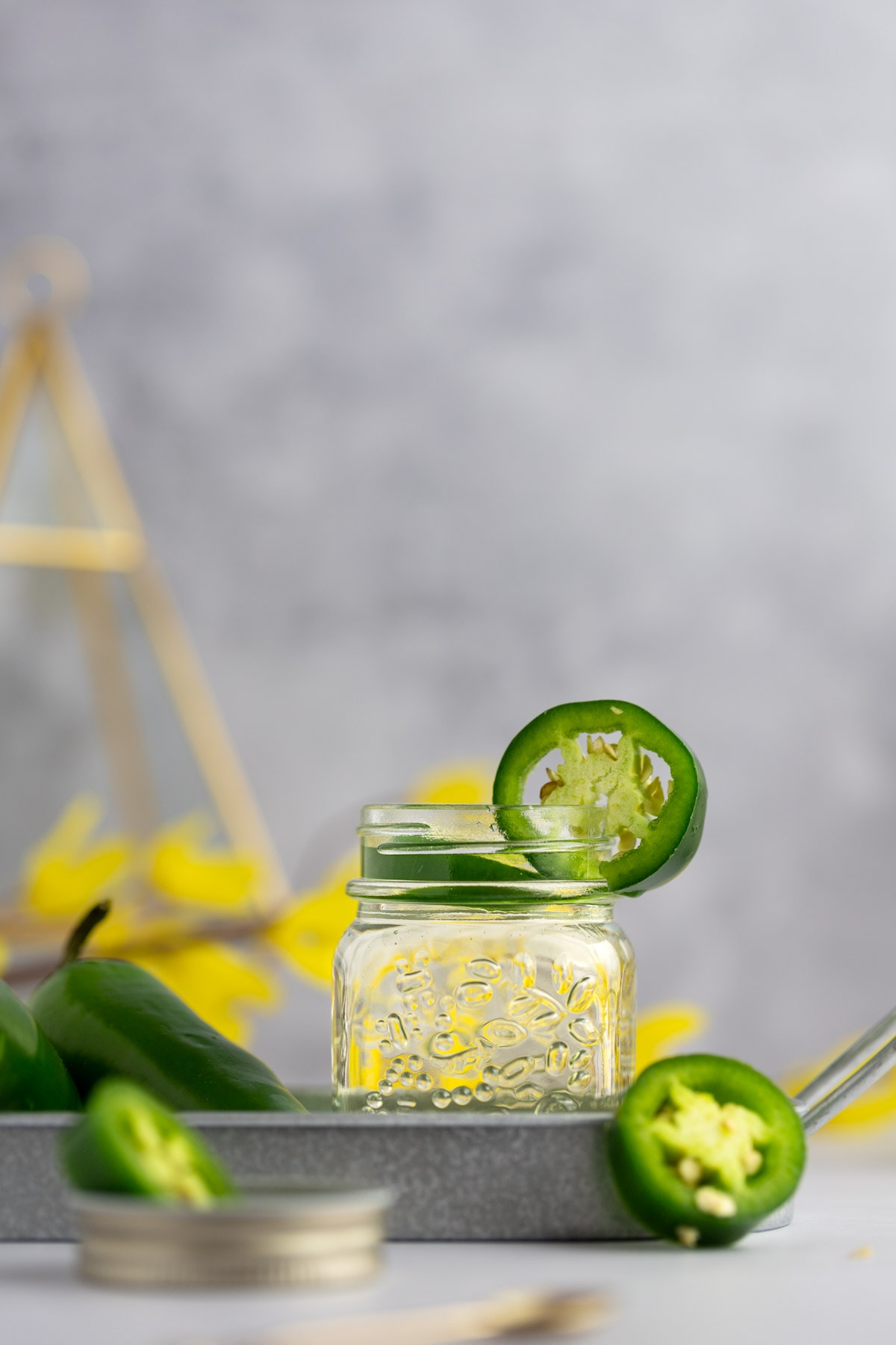 Glass jar of jalapeño simple syrup on a metal tin, garnished with a slice of jalapeño, yellow flowers in the background.