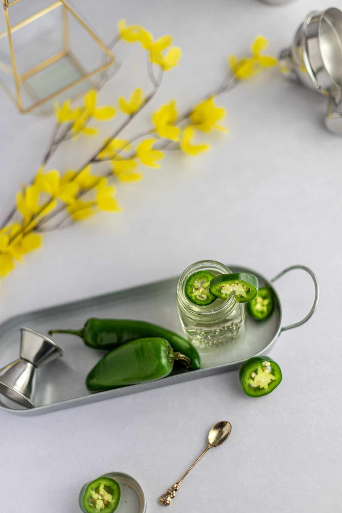 Overhead photo of a jar of syrup, surrounded by jalapeños, a gold spoon, a metal jigger and yellow flowers.