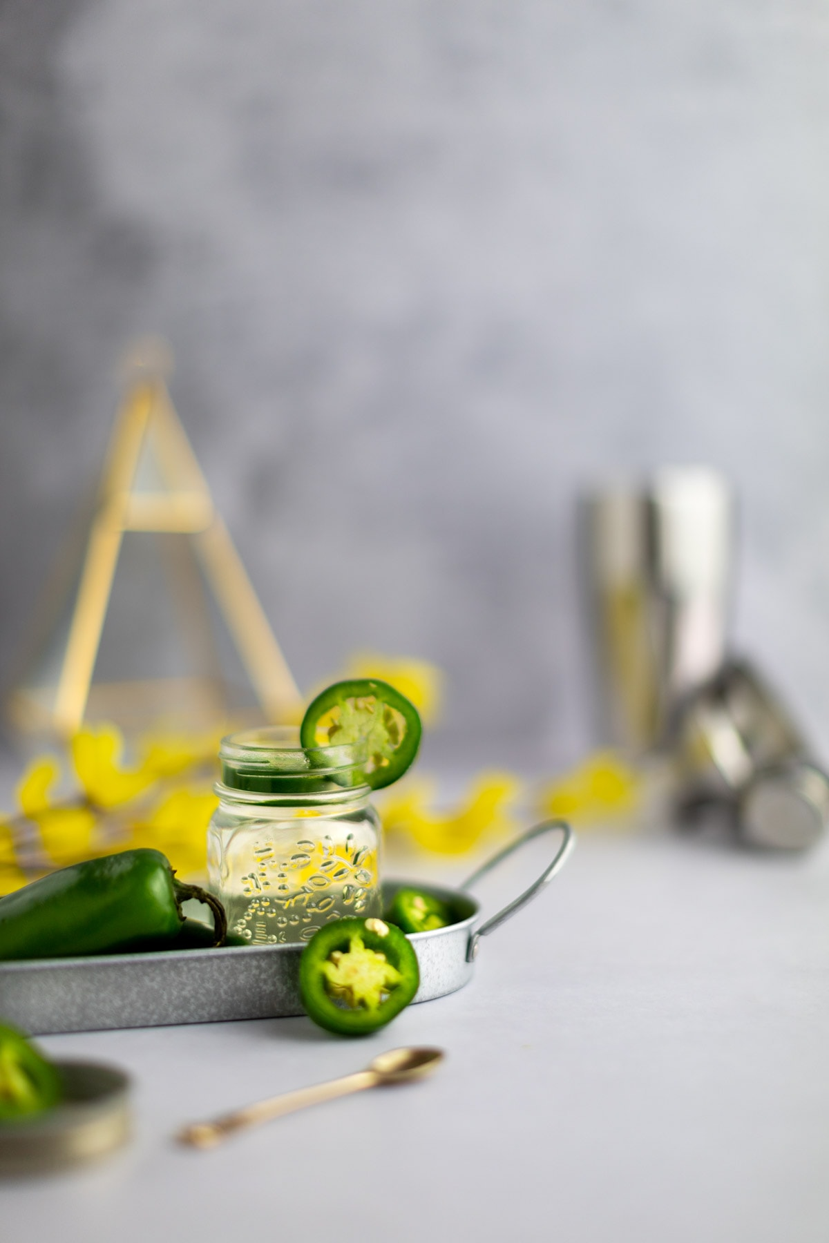 Simple syrup in a glass jar on a tray, with a cocktail shaker and yellow flowers in the background, gold spoon in foreground.