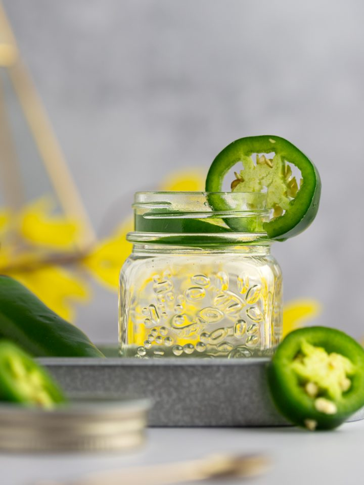 Glass jar of jalapeño simple syrup on a metal tray, next to jalapeño slices, on a grey background.