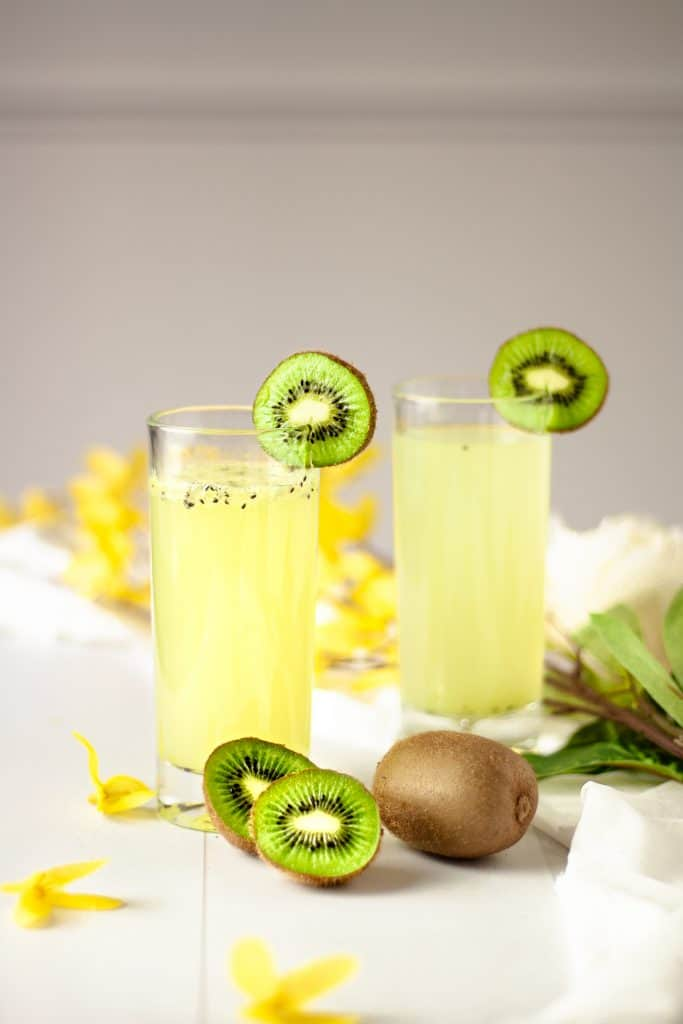Two kiwi gin cocktails garnished with kiwi slices and sitting in a table with scattered yellow flowers.