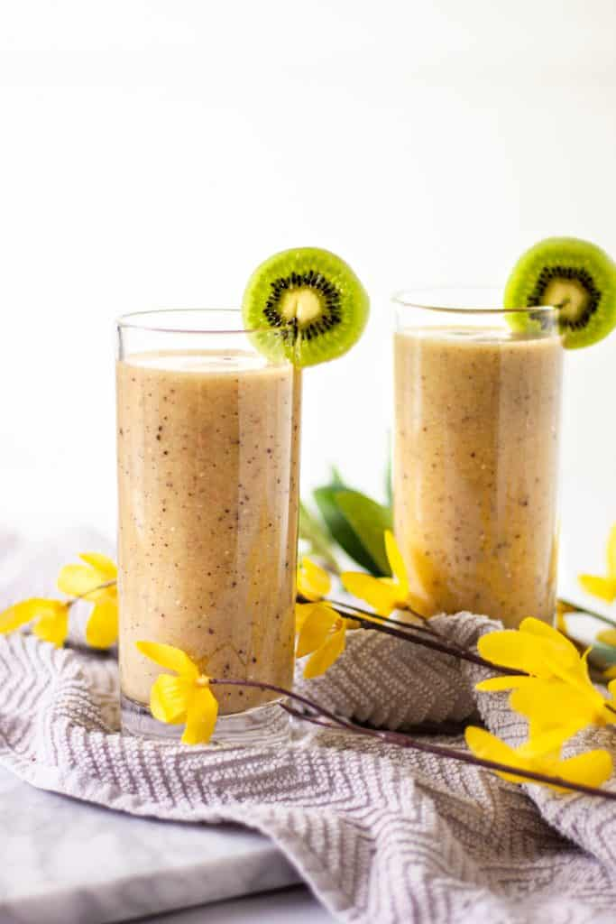 Two glasses of kiwi grapefruit smoothie side by side each other on a grey hand towel with yellow flowers