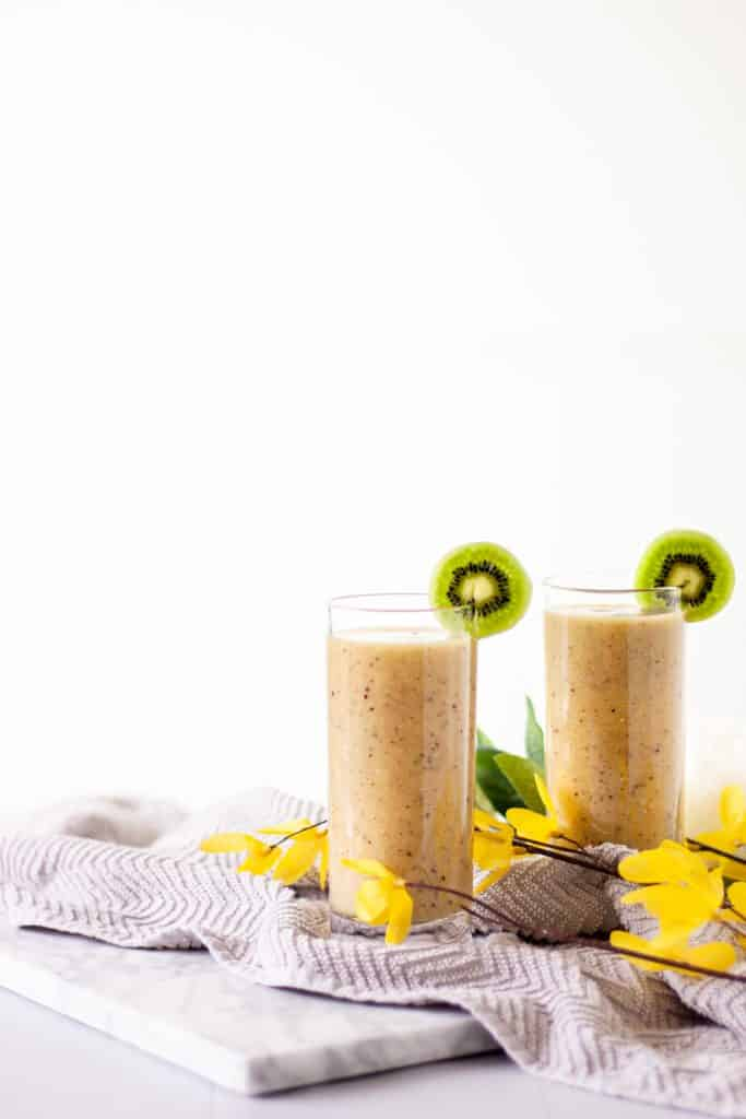 Two glasses of kiwi grapefruit smoothie beside each other on a grey towel and marble cutting board with yellow flowers sitting on top