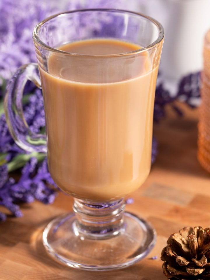 Lavender latte in a glass coffee mug, on a wooden board, with purple lavender in the background.