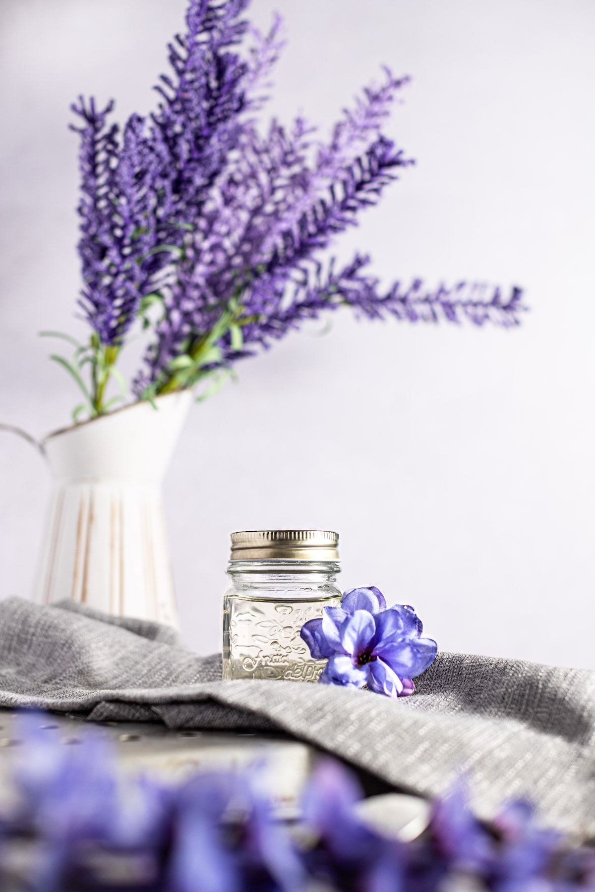 Jar of lavender syrup on a grey napkin, with purple lavender in the foreground, on a light grey background.