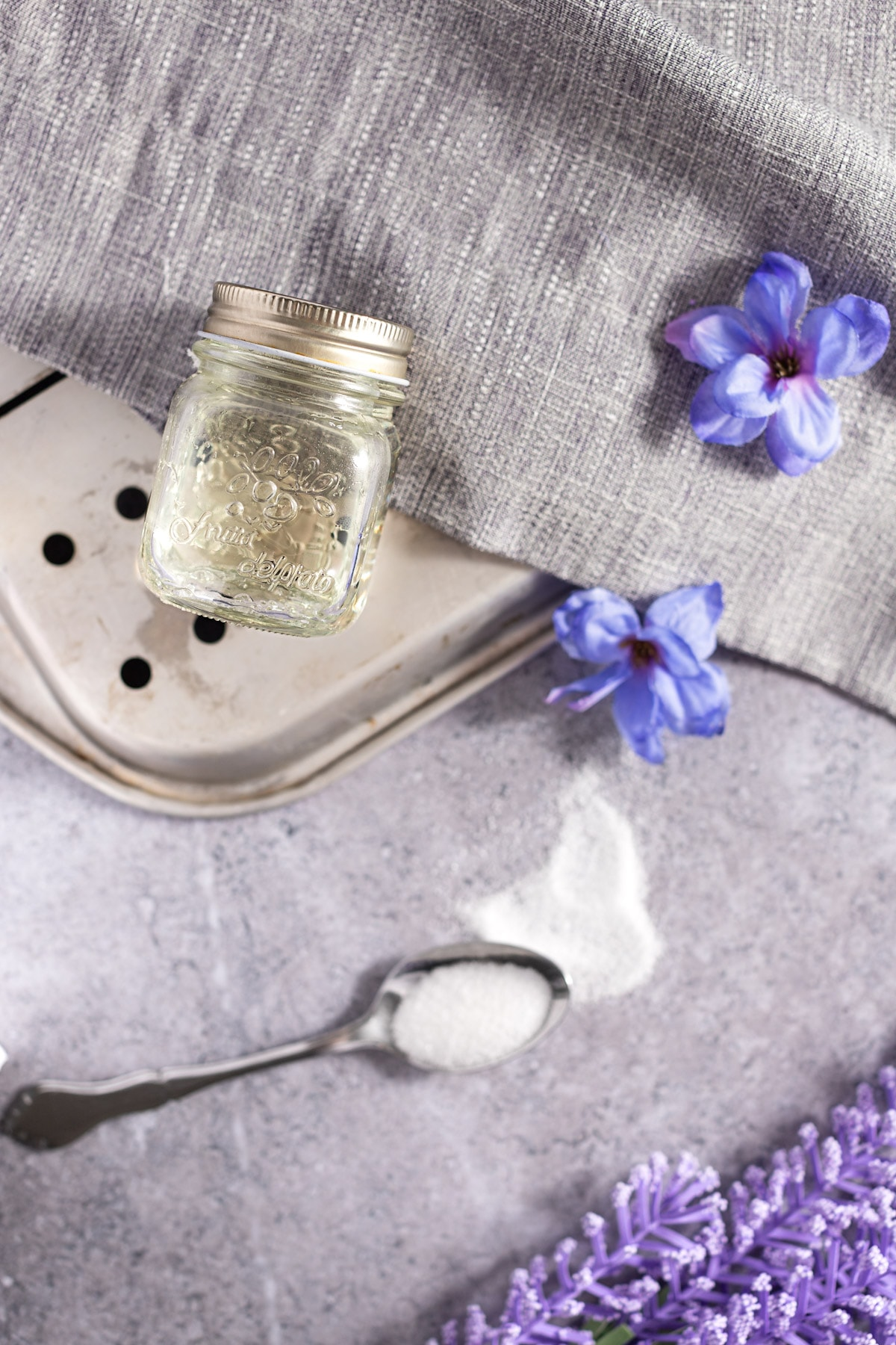Overhead view of a jar of lavender syrup on a flipped over metal tray, next to purple flowers and a metal spoon filled with white sugar.