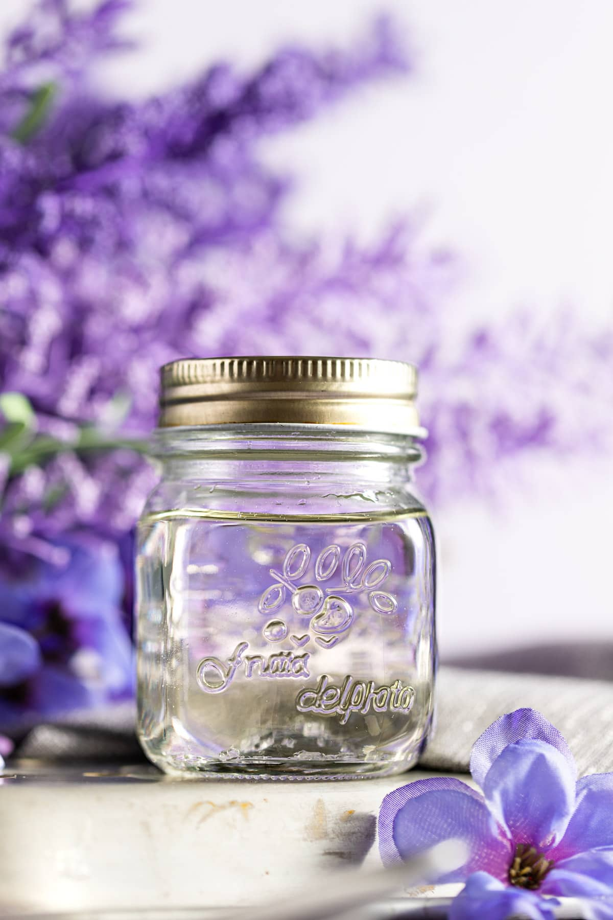 Lavender syrup in a jar, on a metal tray, with purple lavender in the background.