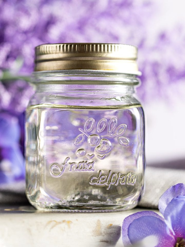 Lavender syrup in a small jar, with purple lavender flowers in the background.