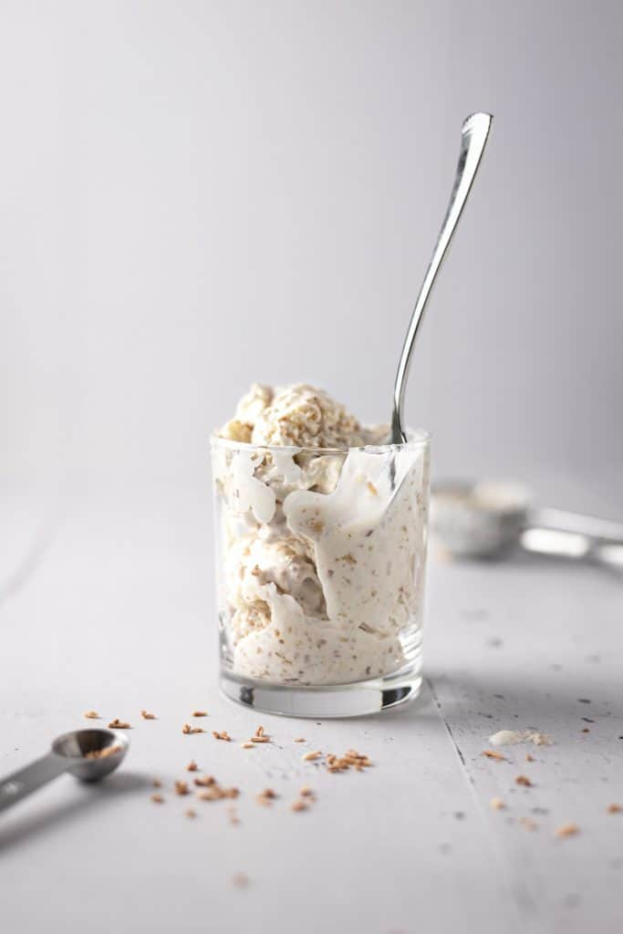 A glass and spoon of macadamia ice cream with toasted coconut scattered around on the table