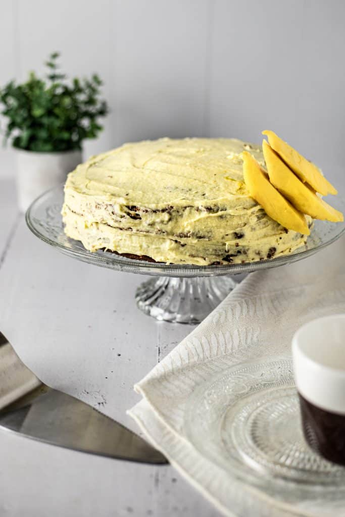 A whole, uncut mango chocolate cake with a couple mango slices on top, sitting on a glass platter