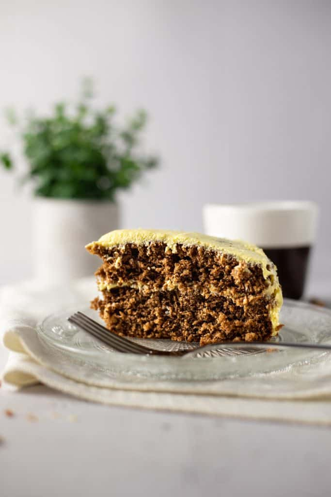 An eye level view of a large slice of mango chocolate cake beside a fork, with a coffee mug and small green plant in the background