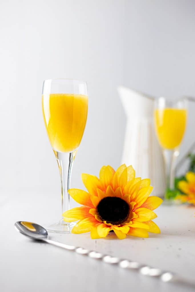 A mango cocktail with a metal spoon in the foreground, a sunflower right next to the stem of the glass and a white jug in the background.