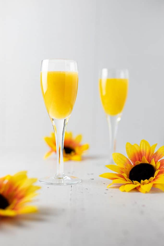 Two glasses of mango gin cocktail with three sunflowers scattered around them.