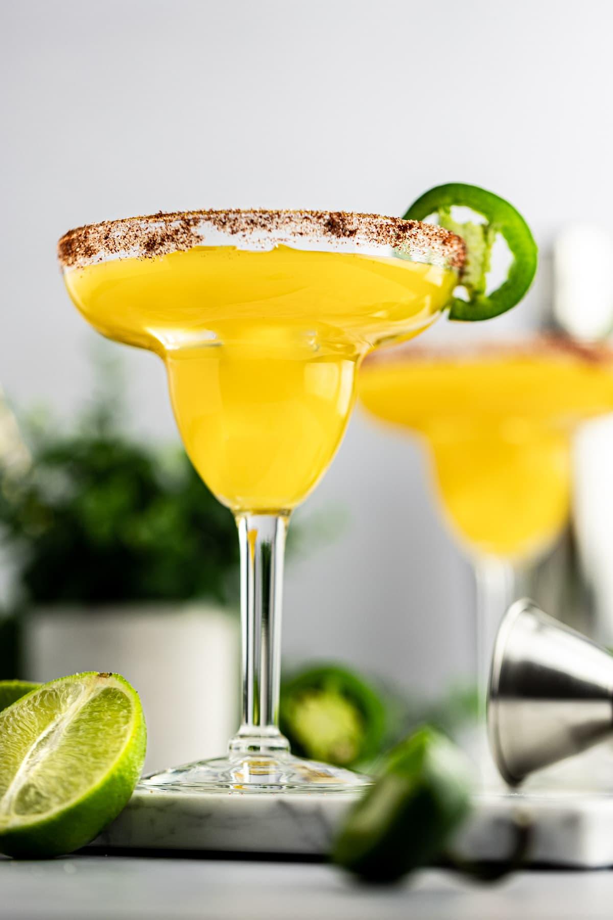 Up close photo of a mango jalapeño margarita, with tajin seasoning on the rim and garnished with a jalapeño.