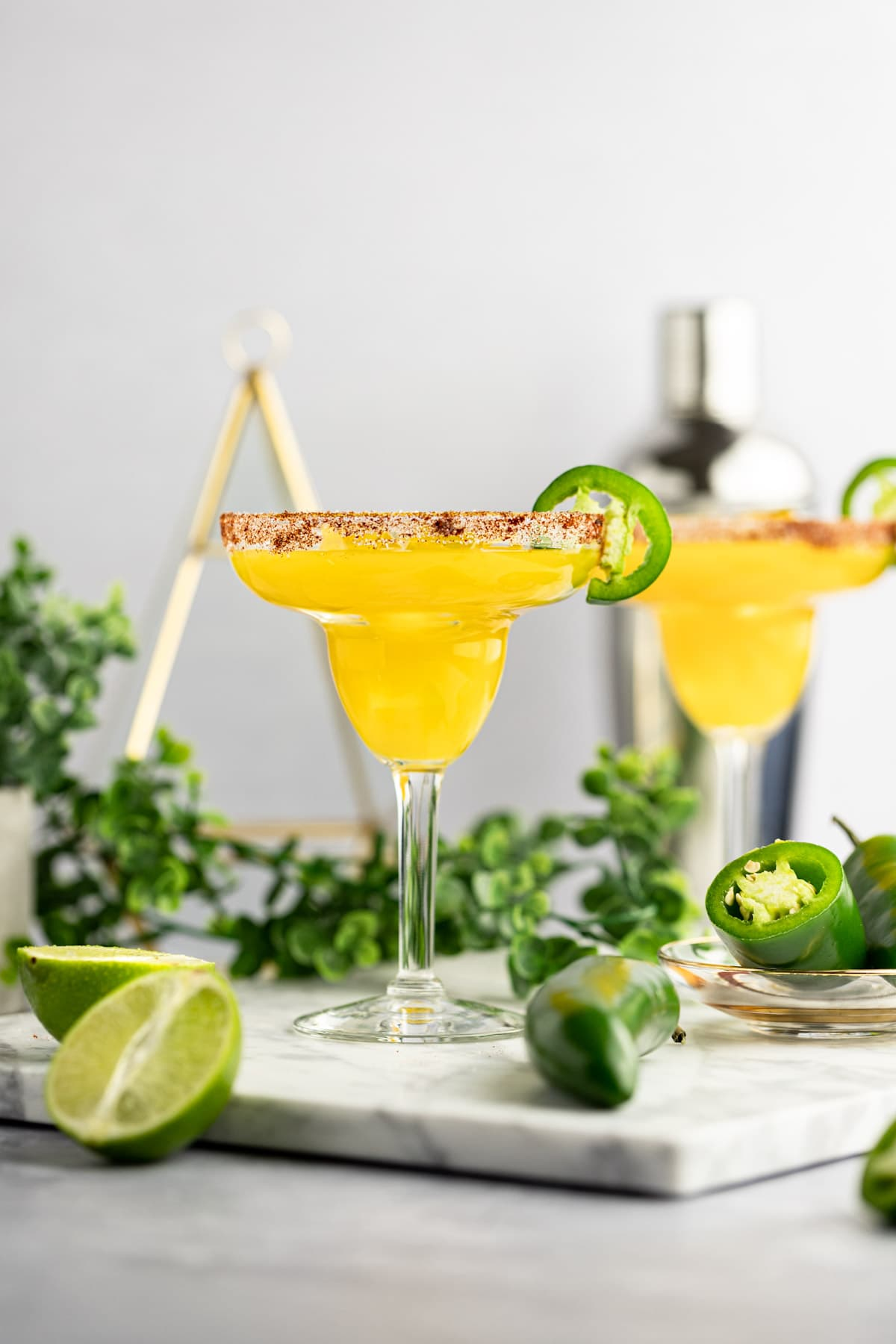 Two margaritas garnished with jalapeños, on a grey marble board, garnished with jalapeño slices, with green plants and a cocktail shaker in the background.