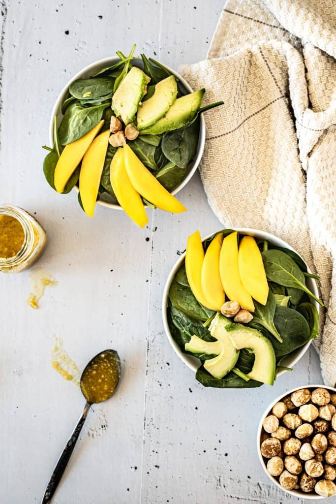 Overhead view of two bowls of mango macadamia salad, a bowl of macadamia nuts, a spoonful of dressing and a brown hand towel