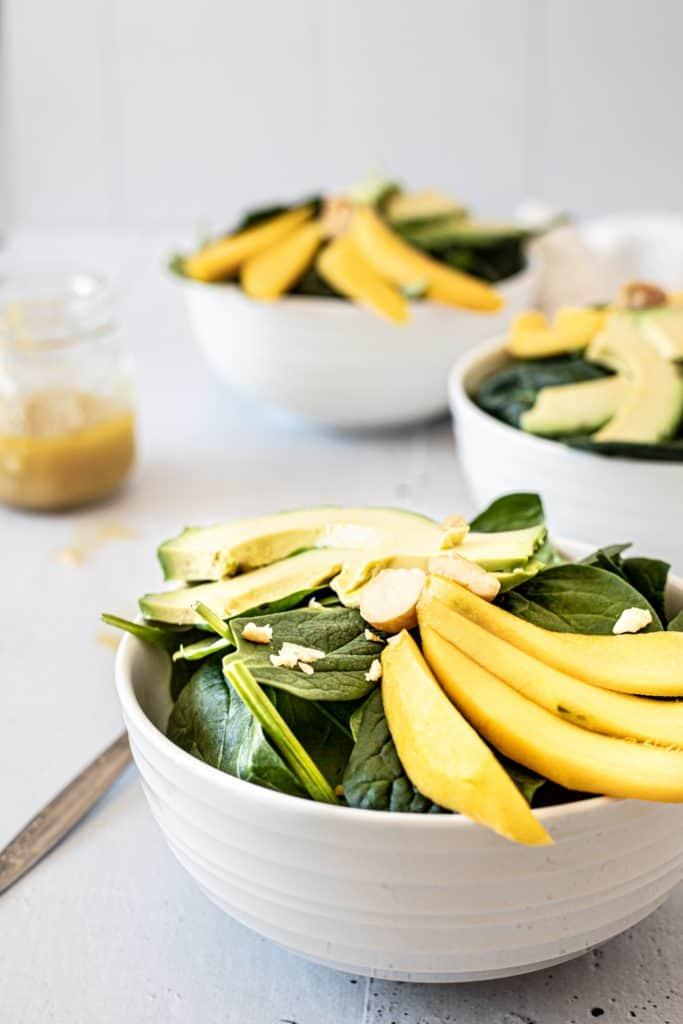 Side view of three bowls of mango macadamia salad on a grey wood table
