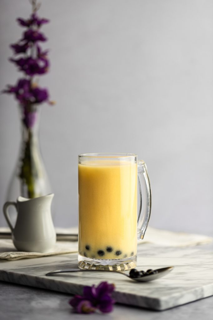 A large yellow mango milk tea on a white marble board, with a spoonful of boba in front and a vase with purple flowers behind.