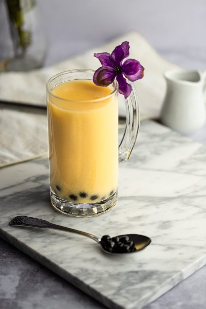 Yellow-orange milk tea with boba on a white marble board, with a spoon of boba, beige napkin in the background.