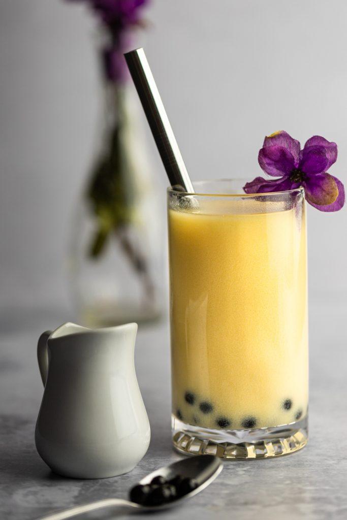 Mango bubble tea with a metal boba straw, purple flower on the rim, next to a small white creamer.