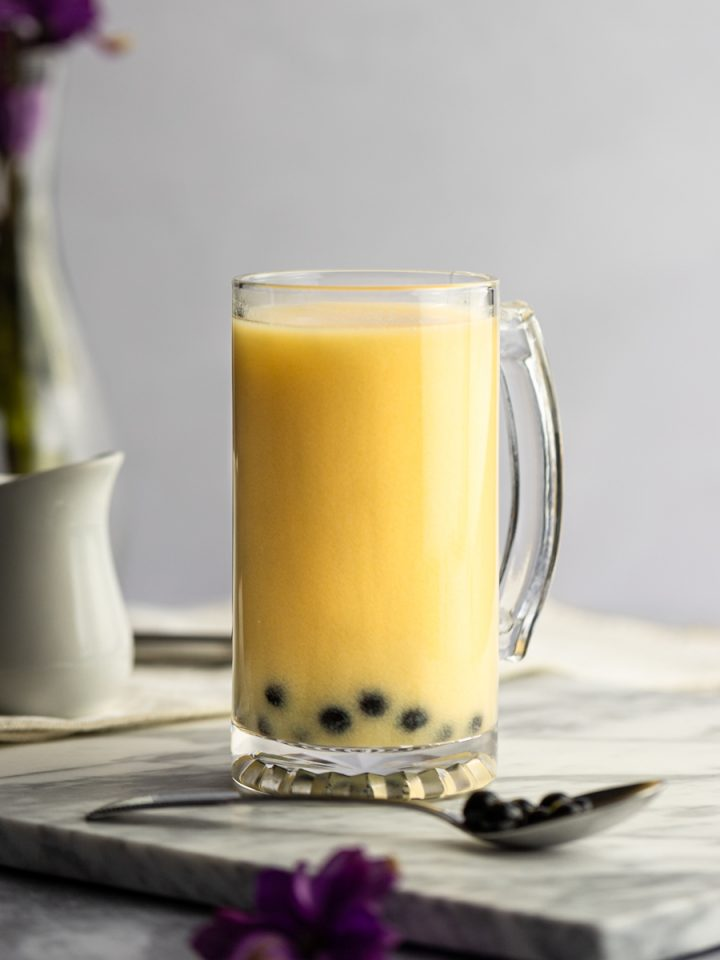 A large mango milk tea with a small creamer and vase of flowers in the background, spoon of boba and purple flower in the foreground.