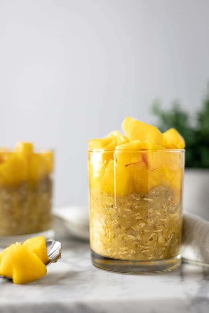 Side angle view of a glass of mango overnight oats, beside a metal spoon full of mango pieces