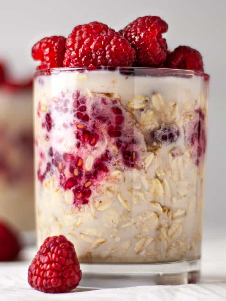 Side angle view of a glass of maple raspberry overnight oats topped with fresh raspberries