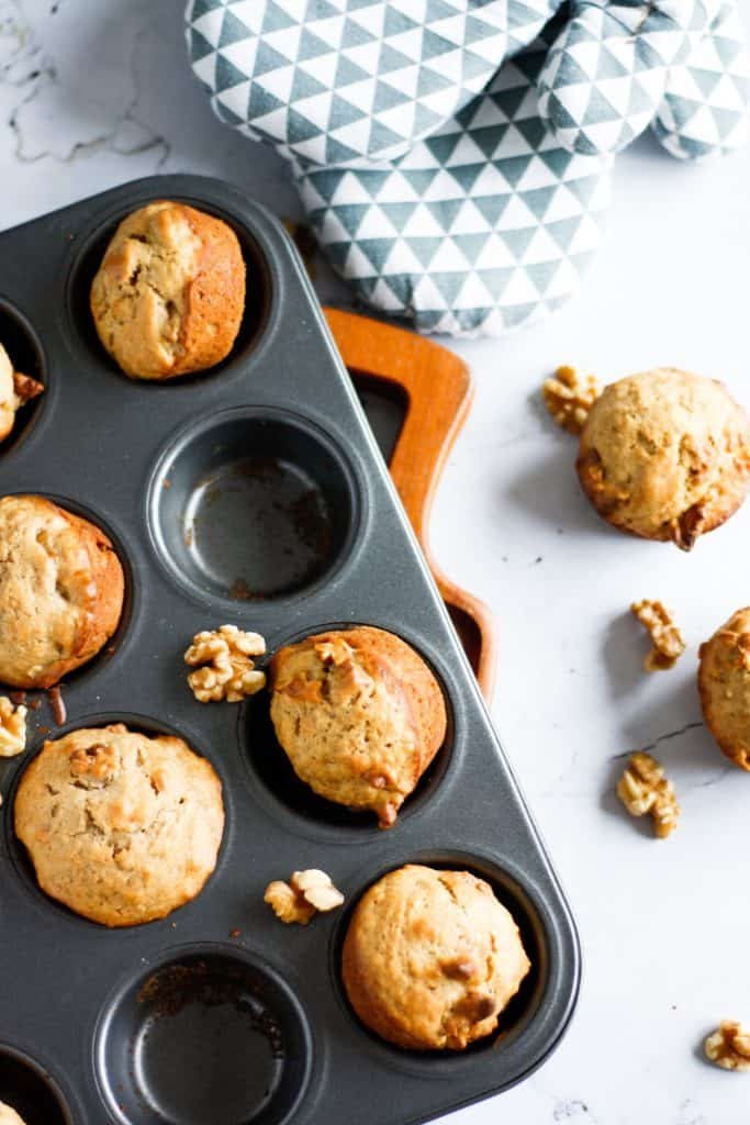 Muffin time of maple walnut muffins with some missing and scattered walnuts on the table