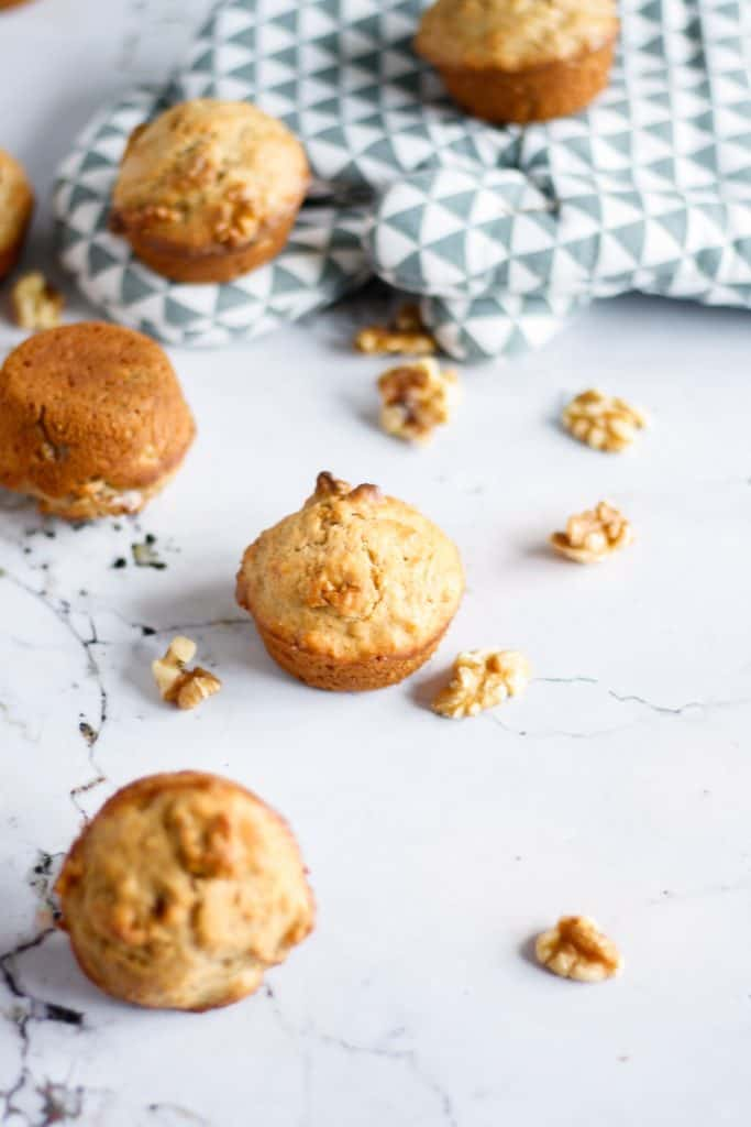 A few maple walnut muffins scattered on the table with walnuts and oven mitts in the background