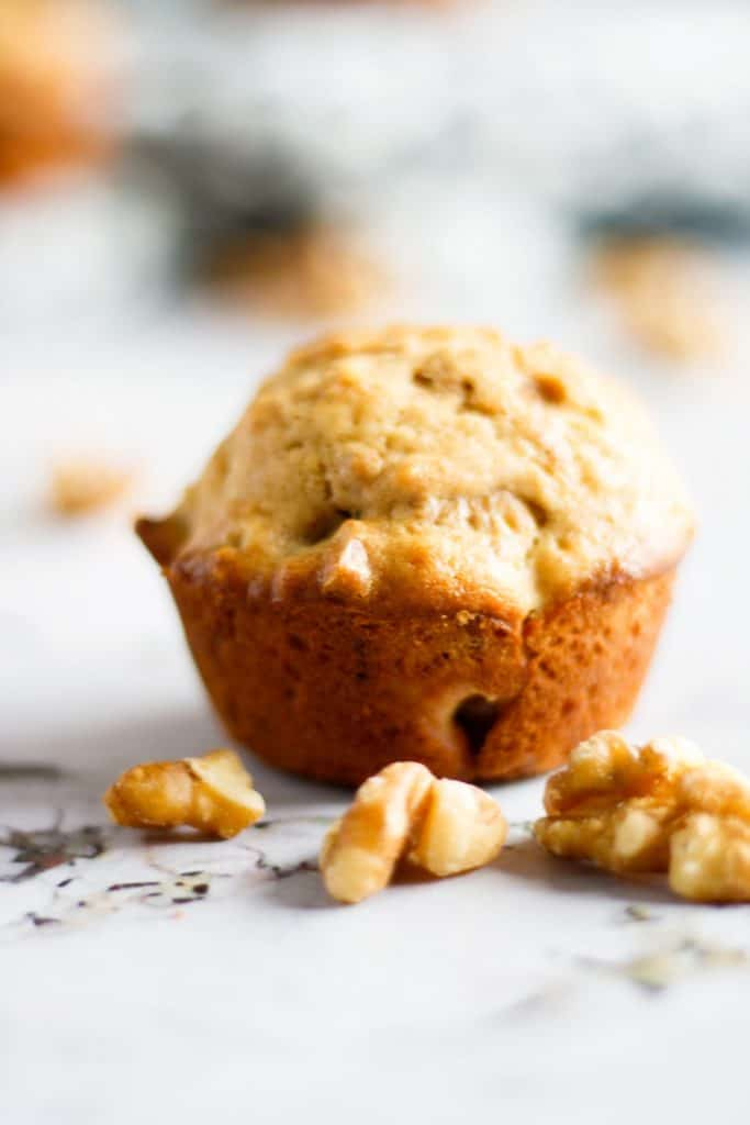 Up close view of individual maple walnut muffin with walnuts on the table in front of it