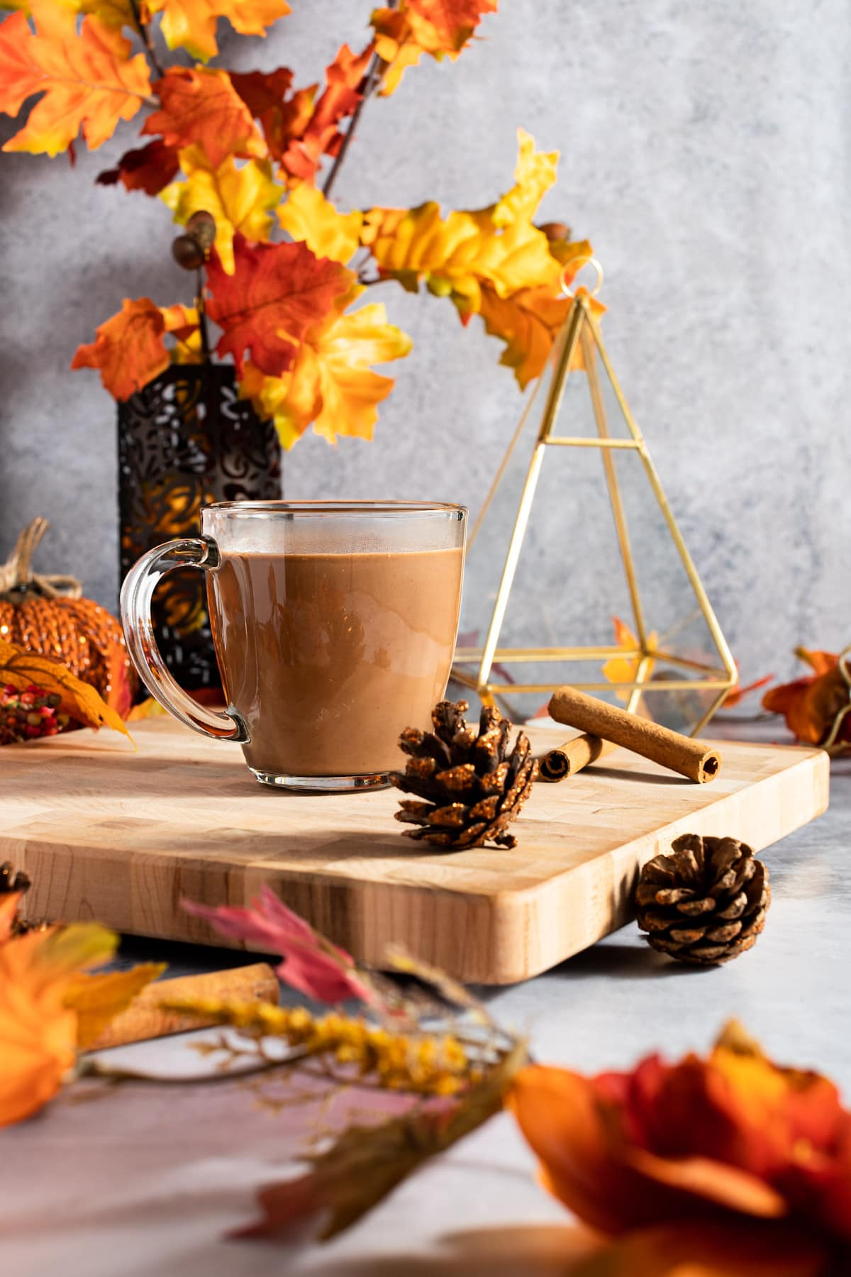Oat milk hot chocolate on a wooden cutting board, next to pinecones and fall leaves.