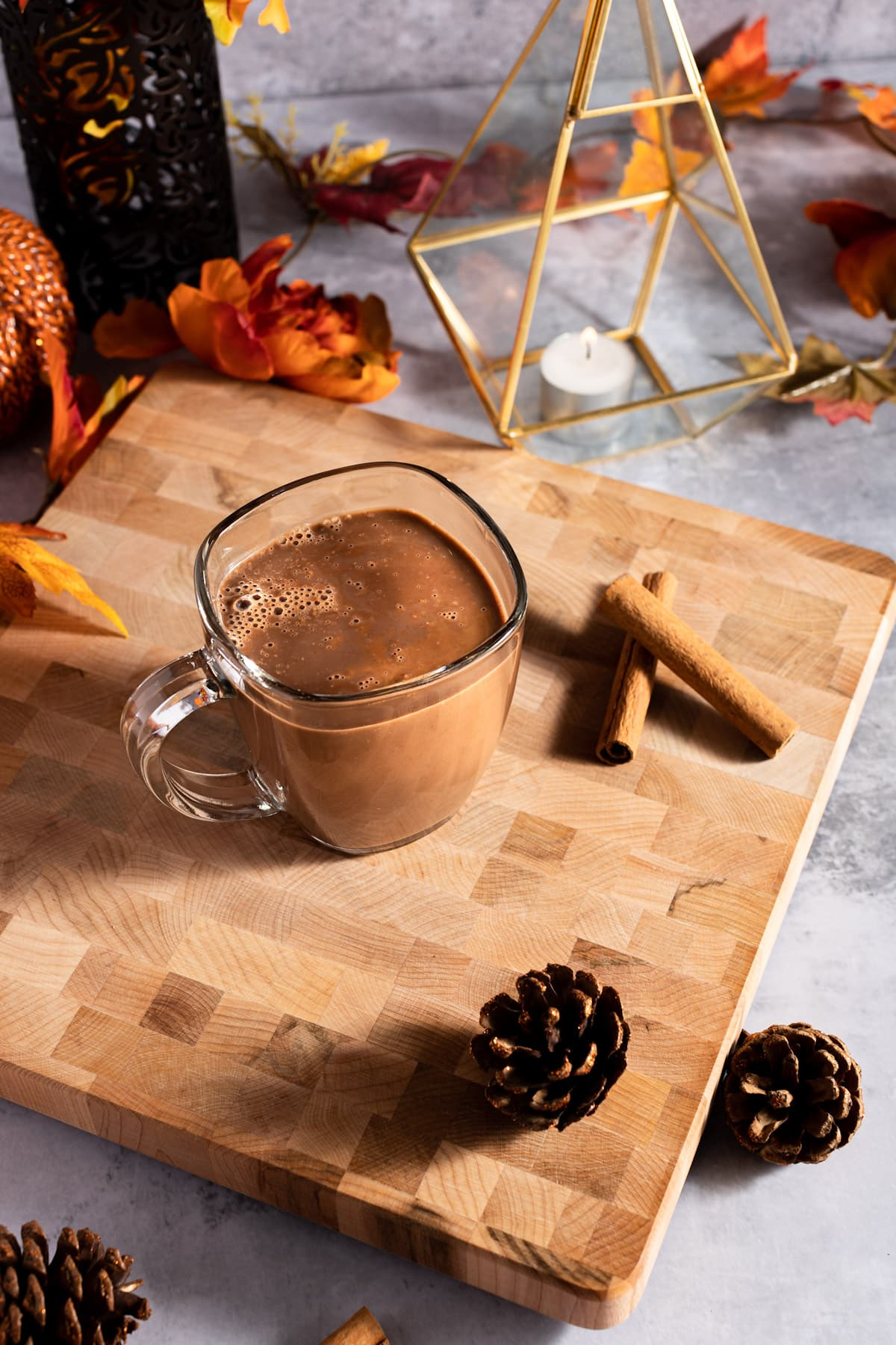 Overhead photo of oat hot chocolate, next to pinecones, cinnamon sticks, a small candle in a golden votive and leaves.