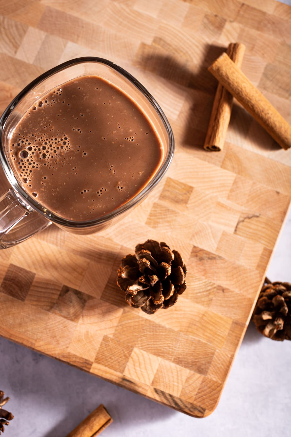 Overhead photo of hot chocolate, cinnamon sticks and a pinecone on a wooden board.