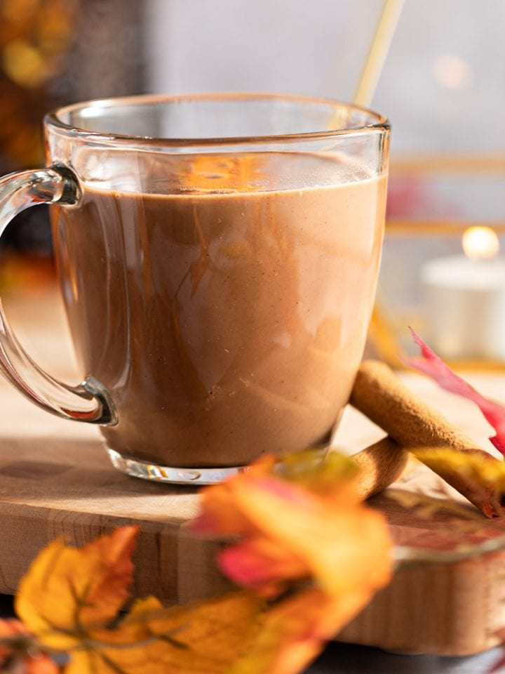 Oat milk hot chocolate on a wooden serving board, next to cinnamon sticks, with fall leaves in the foreground.