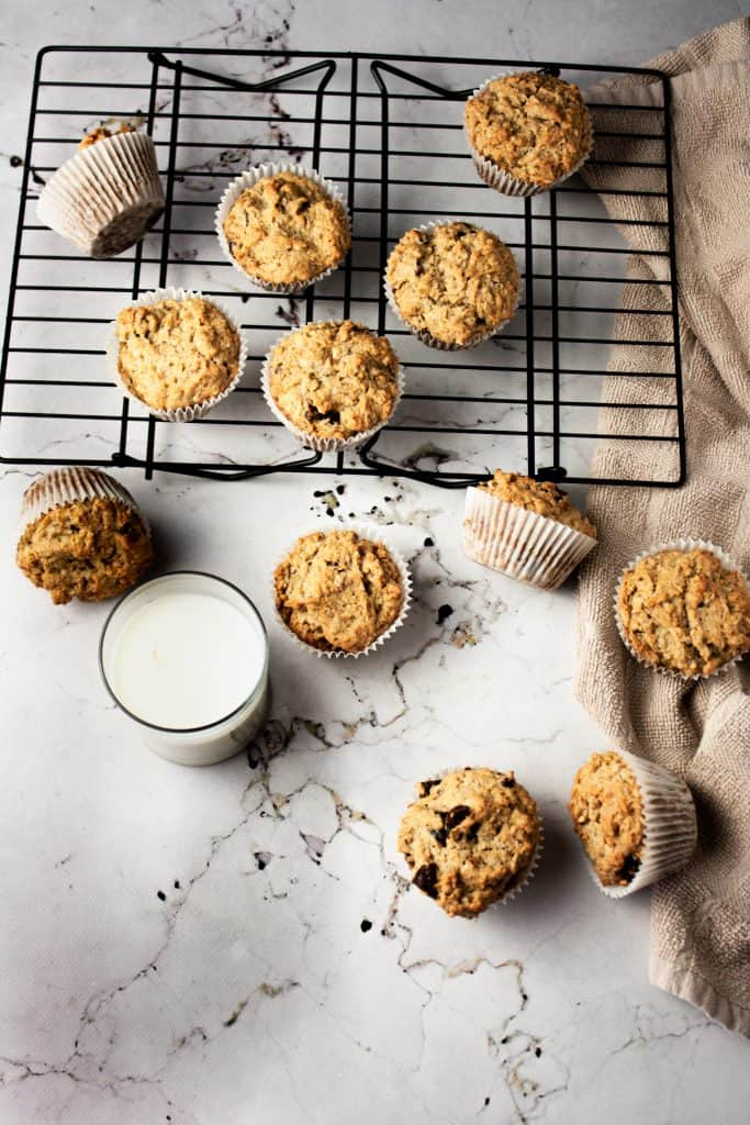 Overhead view of muffins scattered on a white marble table next to a glass of milk