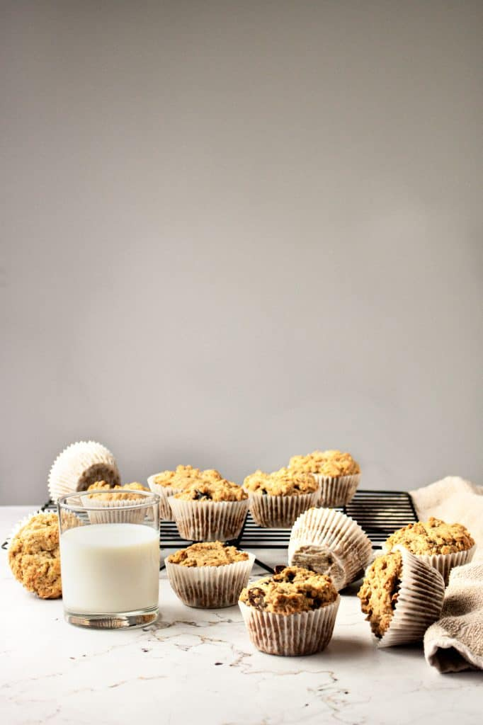 Banana date oatmeal muffins scattered over the table with a glass of milk in the foreground.