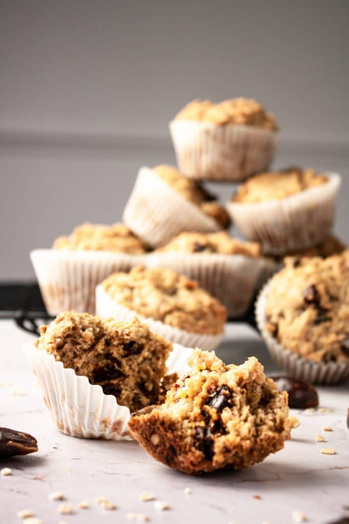 Up close view of a banana oatmeal and date muffin broken open with a stack of muffins in the background