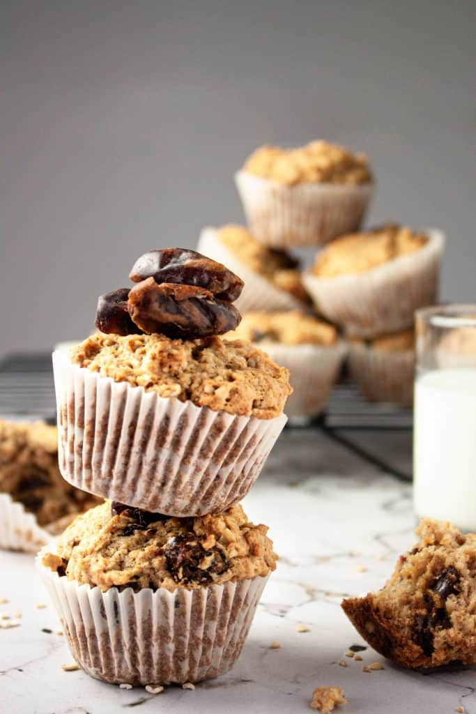 Up close side shot of two banana date oat muffins balanced on top of each other with milk and more muffins stacked in the background.