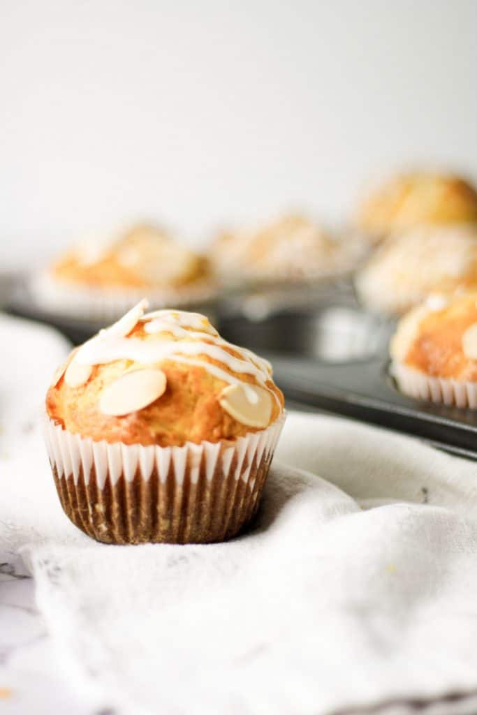 An orange almond muffin on a white hand towel with a full muffin tray in the background