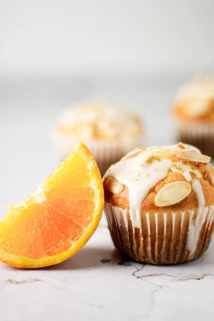 An orange slice leaning on a single orange almond muffin with orange glaze