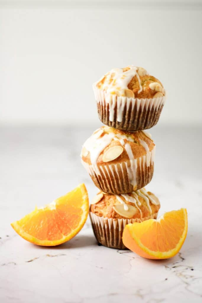 Three orange almond muffins with orange glaze stacked on top of each other next to two orange slices