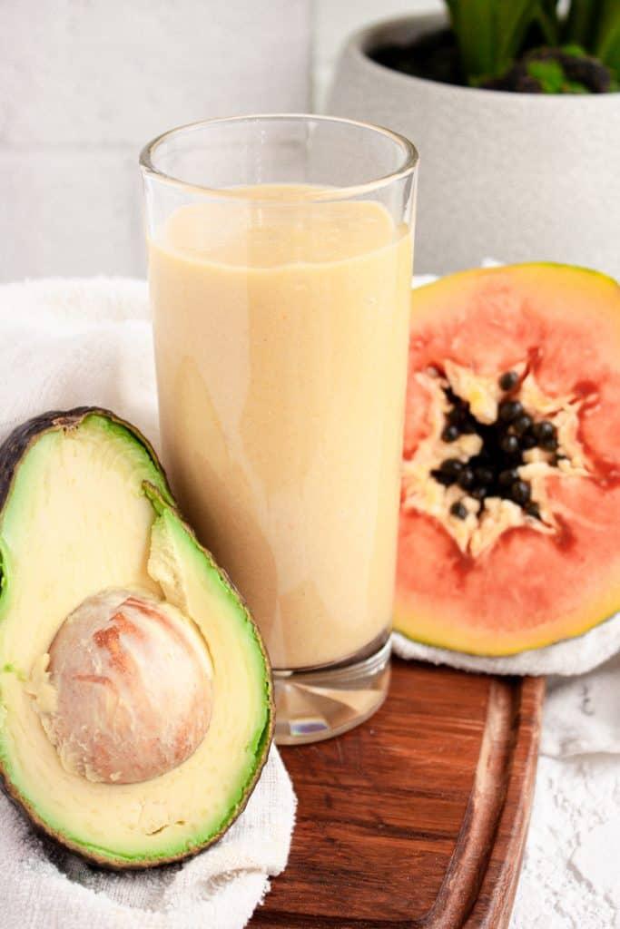 Up close view of a glass of papaya avocado smoothie on a wooden board beside half an avocado and papaya