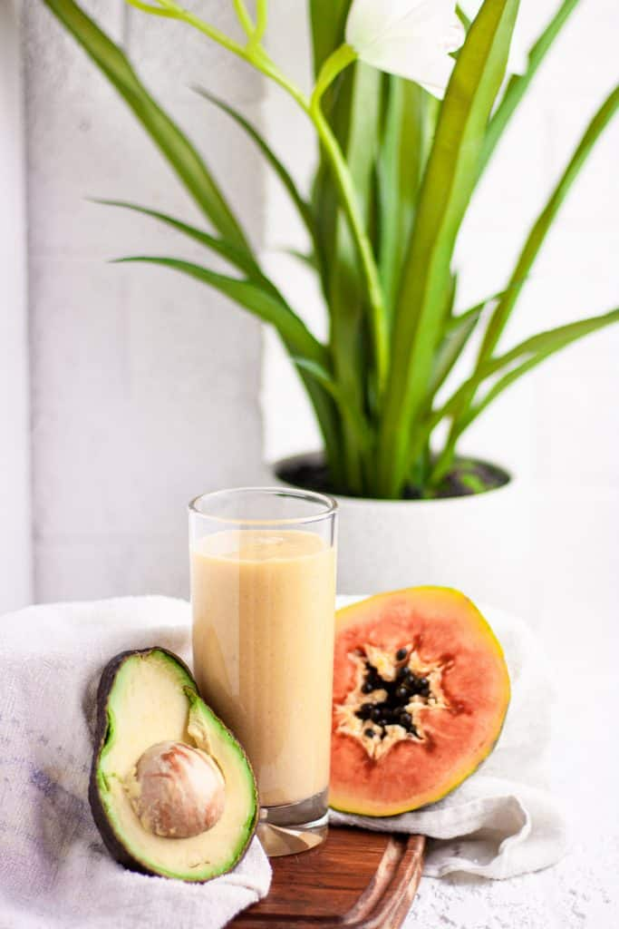 Tall glass of papaya avocado smoothie on a wooden board beside half an avocado and papaya, in front of a white brick wall