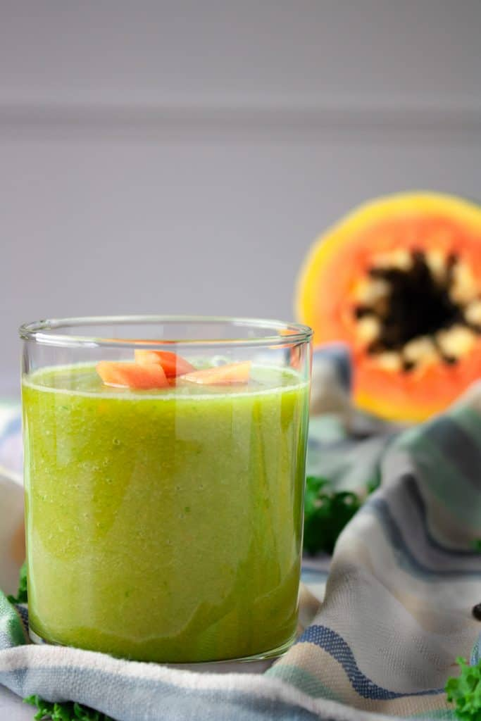 Glass of papaya kale smoothie on a striped hand towel with half a papaya in the background.