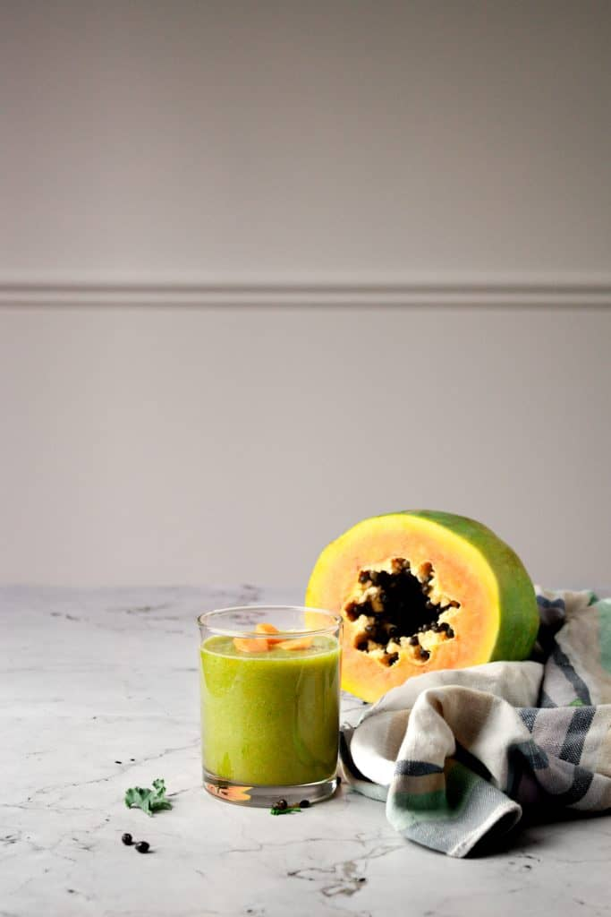 Zoomed out shot of a glass of papaya and kale smoothie, a half papaya and striped linen hand towel on a white marble table