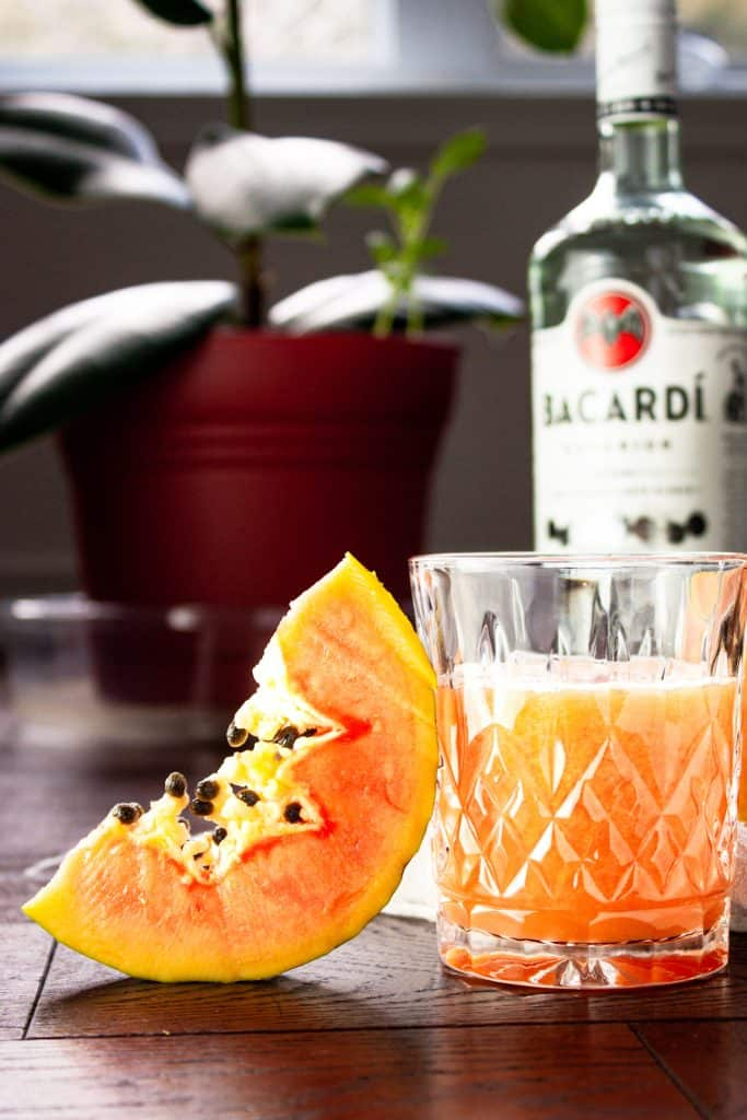 Glass of papaya rum punch beside a papaya slice with a rum bottle and green plant in the background