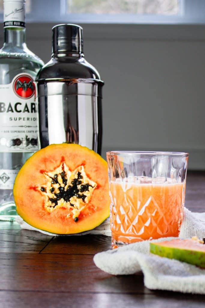 Glass of papaya rum punch beside half a papaya with a rum bottle and cocktail shaker in the background